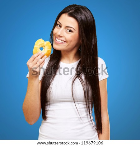 portrait of young woman eating a donut over blue