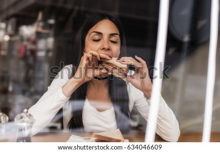 Portrait of young woman eating a sandwich in fast food cafe. Cafe window #634046609