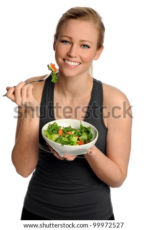 Portrait of young woman eating salad from bowl isolated over white background