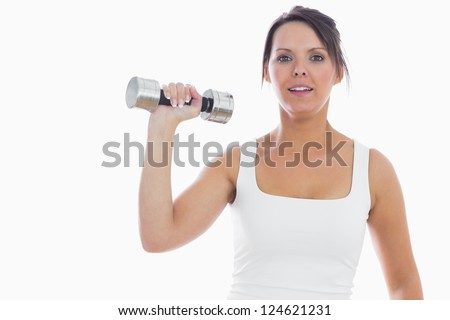 Portrait of young woman exercising with dumbbell over white background