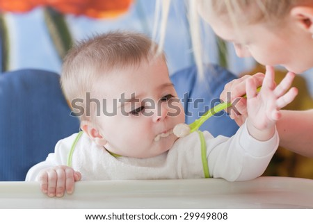 Portrait of young woman feeding her baby son