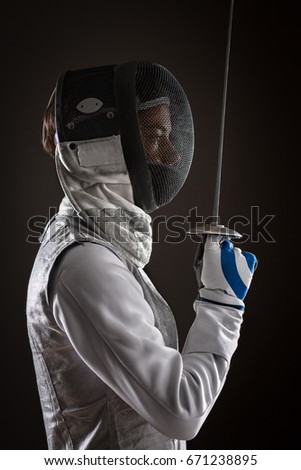 Portrait of Young woman fencer wearing white fencing Mask and costume standing aside and holding the sword in front of her. Black Background