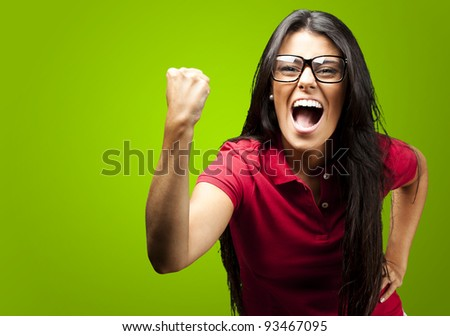 portrait of young woman gesturing victory against a green background