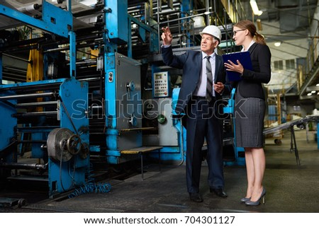 Portrait of young woman giving a tour of modern factory to senior businessman  wearing hardhat