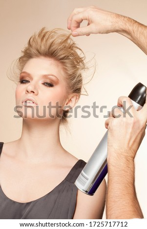 Portrait of young woman having hair styled in studio
