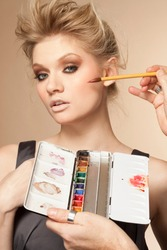 Portrait of young woman having make up applied in studio