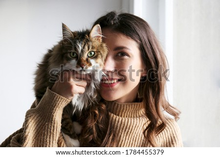 Portrait of young woman holding cute siberian cat with green eyes. Female hugging her cute long hair kitty. Background, copy space, close up. Adorable domestic pet concept.