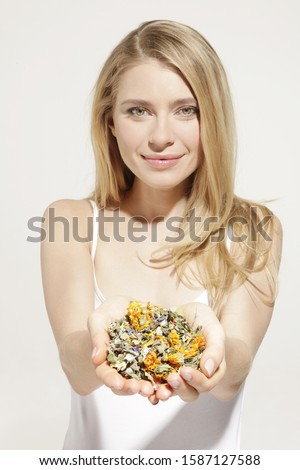 Portrait of young woman holding dried herbs