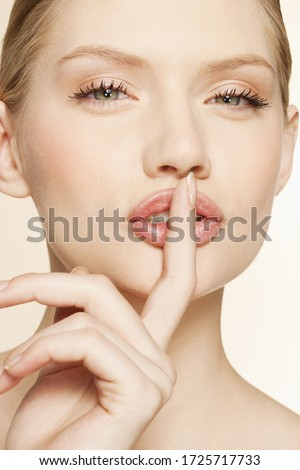 Portrait of young woman holding finger to lips