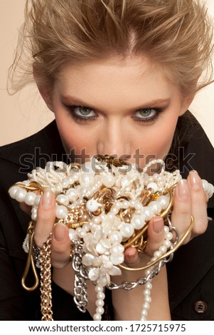 Portrait of young woman holding handfuls of jewelry