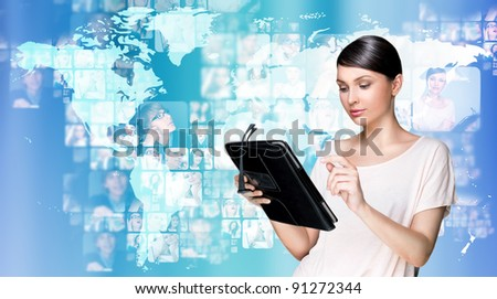 Portrait of young woman holding her tablet computer and communicating with her friends across the world. Standing against world map with photo of people. International communications concept