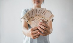 Portrait of young woman holding money banknotes. Showing bunch of baht banknotes at camera.profit and finance.