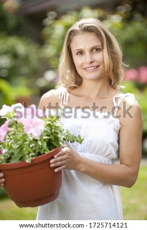 Portrait of young woman holding plant pot, smiling