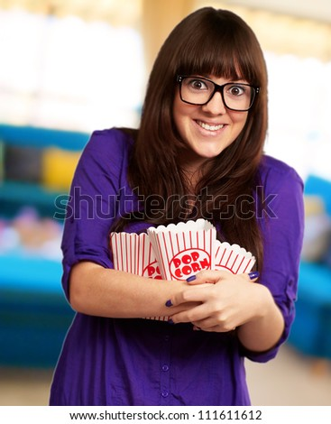 Portrait Of Young Woman Holding Popcorn Container, Indoor