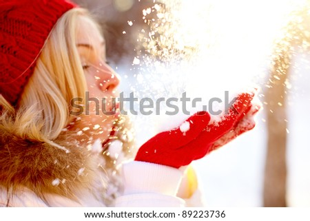 Portrait of young woman holding snow on palms and blowing it
