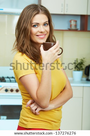 Portrait of young woman holds a cup with coffee or tea against kitchen background. - stock photo