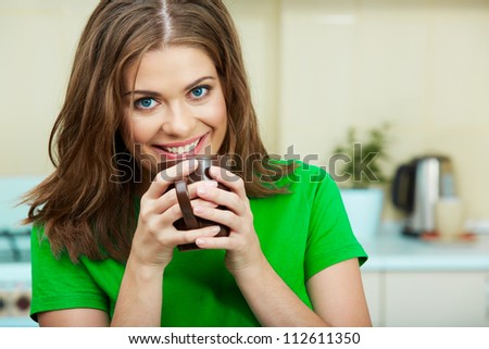Portrait of young woman holds a cup with coffee or tea against kitchen background. Close up face toothy smile