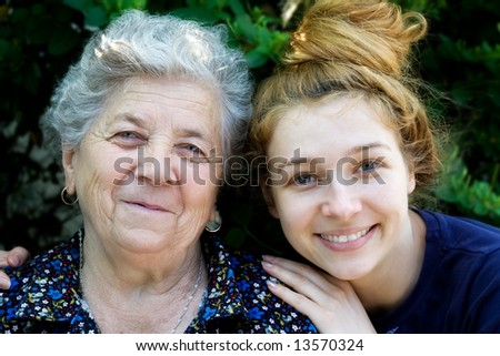 Portrait of young woman hugging her grandmother