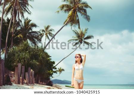 portrait of young woman in bikini and sunglasses on coastline near ocean #1040425915