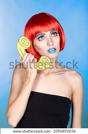 Portrait of young woman in comic comic pop art make-up style. Female in red wig on blue background calls by phone