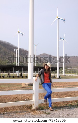 Portrait of young woman in front of windmill