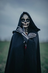 Portrait of young woman in Halloween costume of death with painted skeleton on her body and sugar skull makeup. Halloween concept.
