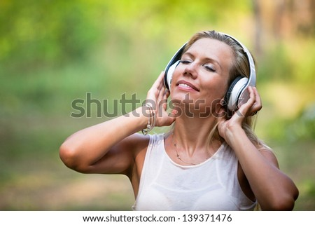 portrait of young woman in headphones enjoying the music - stock photo