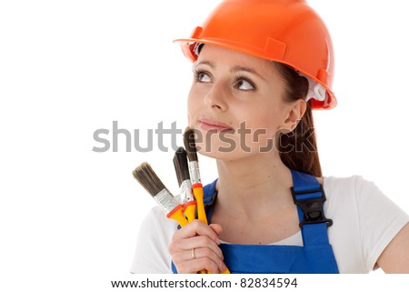 Portrait of young woman in  helmet with paintbrushes on a white background. Female construction worker. - stock photo
