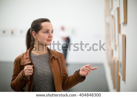 Portrait of young woman in leather jacket at gallery exhibition