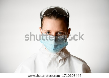 Portrait of young woman in medical mask with safety glasses and in white protective suit on grey background.