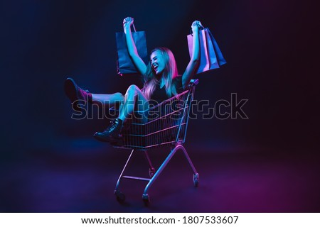 Portrait of young woman in neon light on dark backgound with shopping bags, black friday
