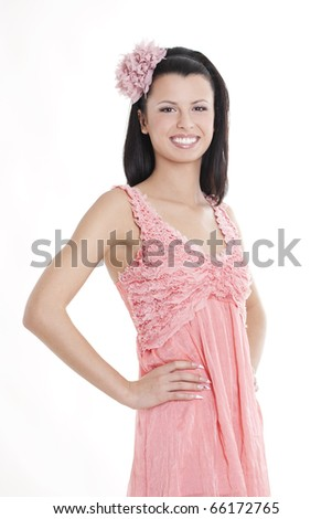 Portrait of young woman in pink dress smiling against white background