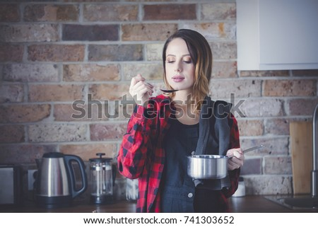 Portrait of young woman in red shirt at kitchen. Christmas time #741303652