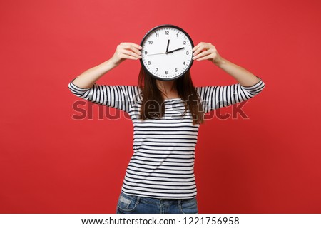 Portrait of young woman in striped clothes hiding, covering face with round clock isolated on red wall background. Time is running out. People sincere emotions, lifestyle concept. Mock up copy space