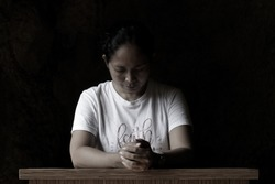 Portrait of young woman kneeling and praying in silent prayer pose, on black art background. Believe in God concept with person praying.
