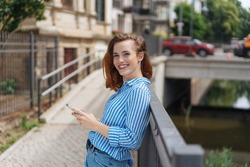 portrait of young woman laughing with smartphone