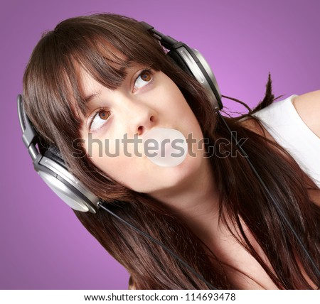 portrait of young woman listening to music with bubble gum over purple