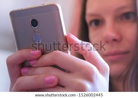 Portrait of young woman looking at mobile phone screen with interest. She looks through and reads attentively messages in smartphone holds it in hands.