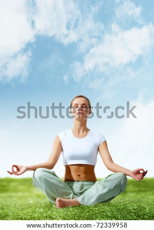 Portrait of young woman meditating in pose of lotus on green grass