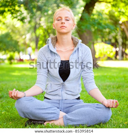 Portrait of young woman meditating in pose of lotus on green grass on meadow at summer park under tree