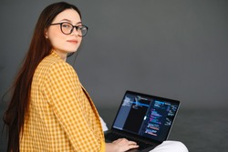 Portrait of young woman mobile developer with laptop, writes program code on a computer, programmer work.
