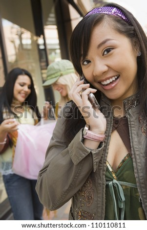 Portrait of young woman on call with female friends in background