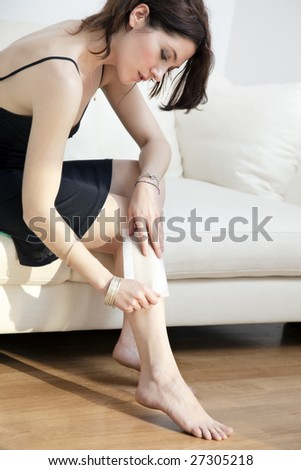 portrait of young woman on sofa having her legs waxed