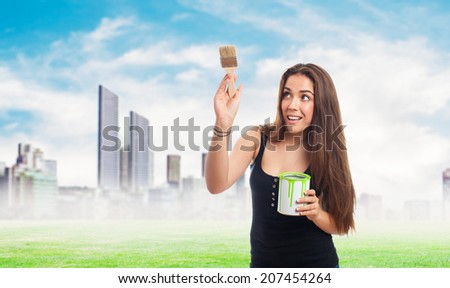 portrait of young woman painting and holding a paint can
