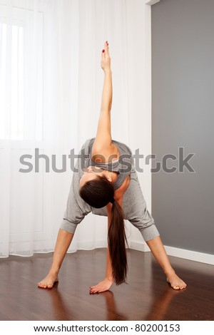 portrait of young woman practicing yoga in room