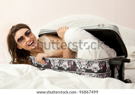 Portrait of young woman preparing for a trip and hiding inside her suitcase