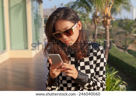portrait of young woman reading message on mobile phone use for modern digital connecting technology