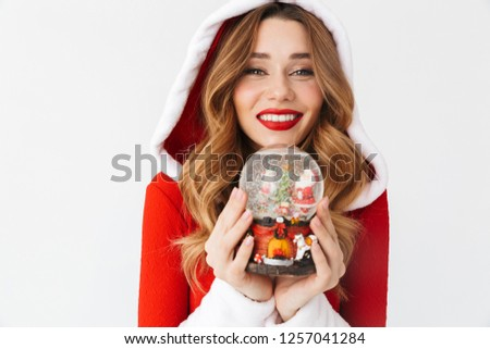 70c3dd4c9167f Portrait of young woman 20s wearing Santa Claus red costume smiling and  holding Christmas snow ball