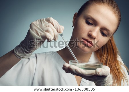 Portrait of young woman - scientist with dropper working at the laboratory. Studio shot