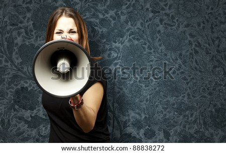 portrait of young woman shouting with megaphone against a vintage wall